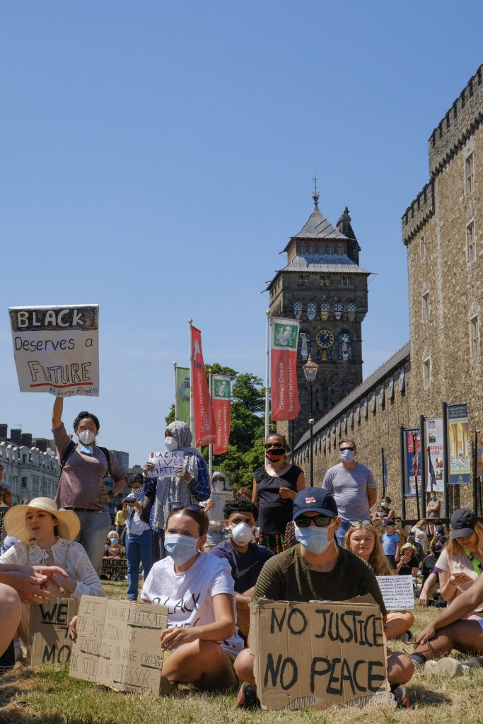 Protestors sitting in front of Cardiff Castle with placards No Justice, No Peace