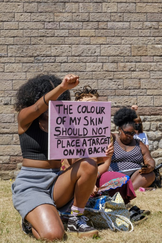 """Black woman on knees with raised fist and sign """"The colour of my skin should not place a target n my back"""""""