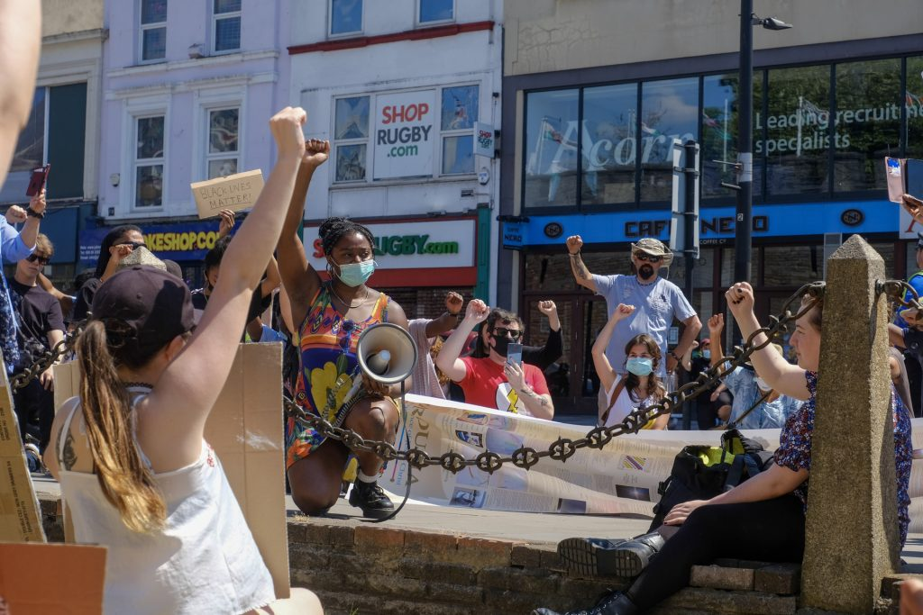 People with raised fists in front of storefront in Cardiff, Wales