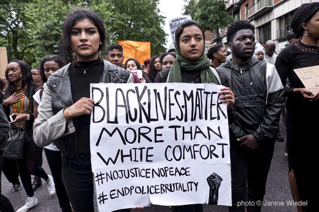 Womem holding sign saying black lives matter more than white comfort
