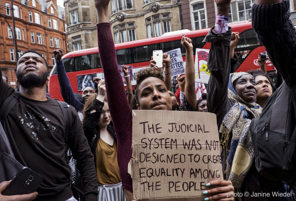 """Protesters in front of London bus with sign """"The Judicial system was not designed to create equality among the people."""""""