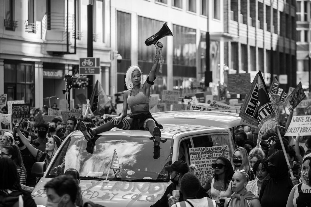 A woman with a megaphone sits on the roof of a van during a Black Lives Matter demonstration,