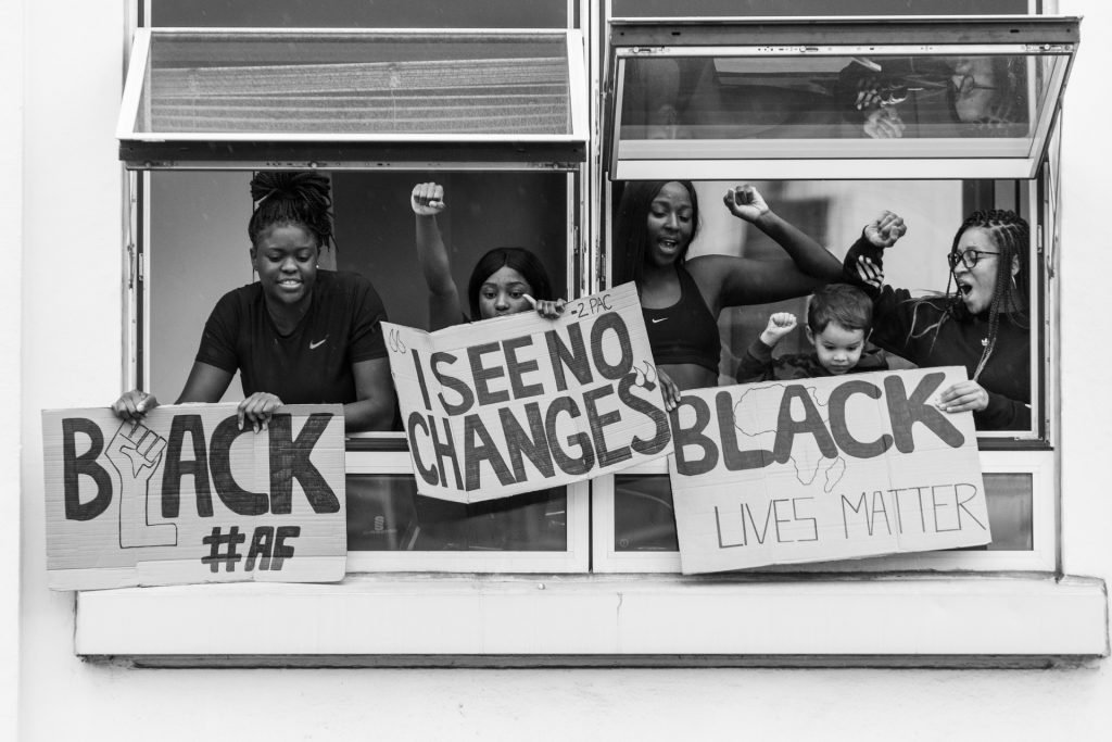 People with raised fists  hanging pro-Black Lives Matter signs outside a window