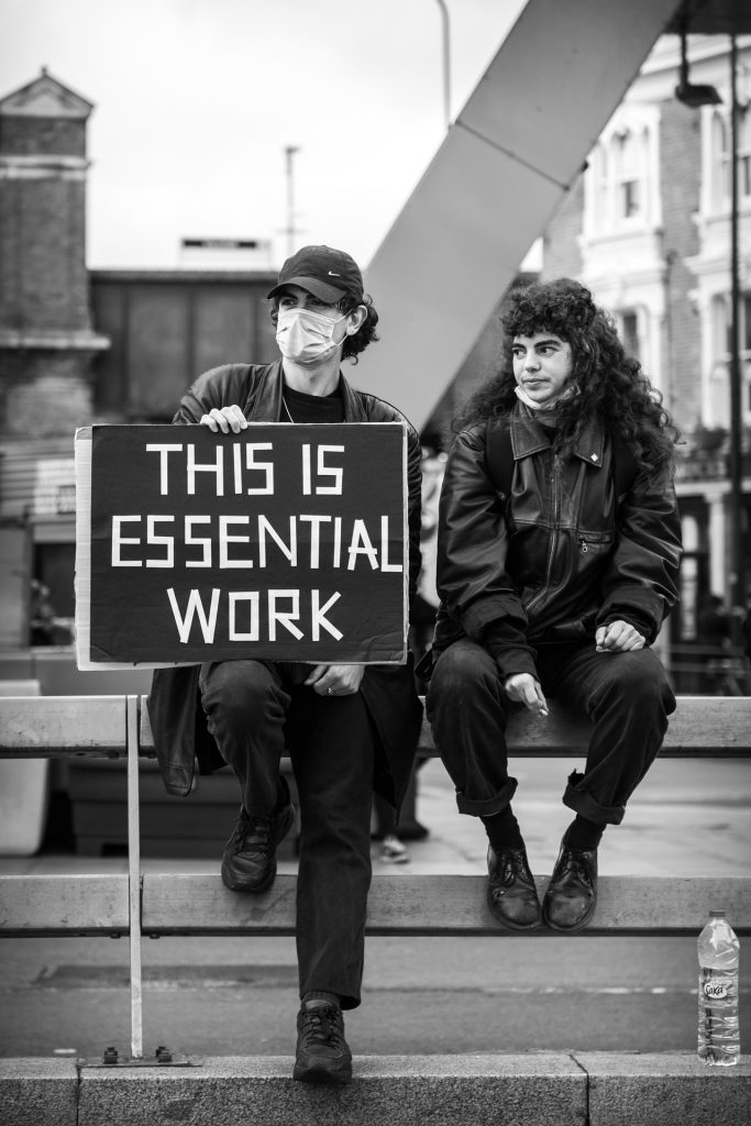 """Two essential workers sitting with sign that says """"This is essential work."""""""