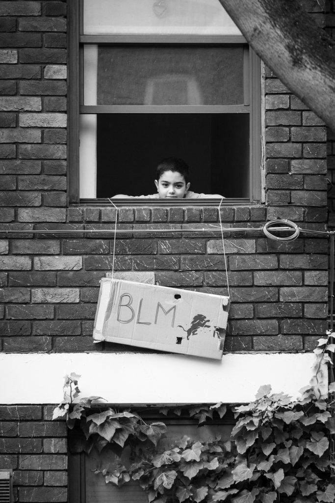 Boy peering out of window over BLM sign above ivy covered wall
