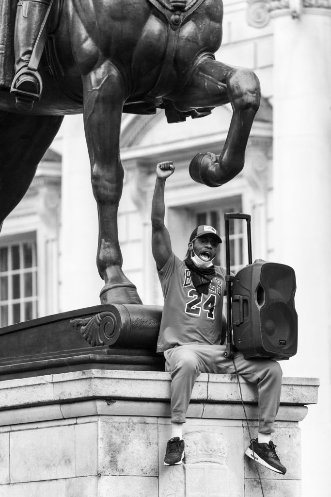 A protester raises his fist under an equestrian statue