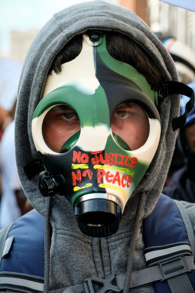 Man wearing mask with No Justice No Peace Written