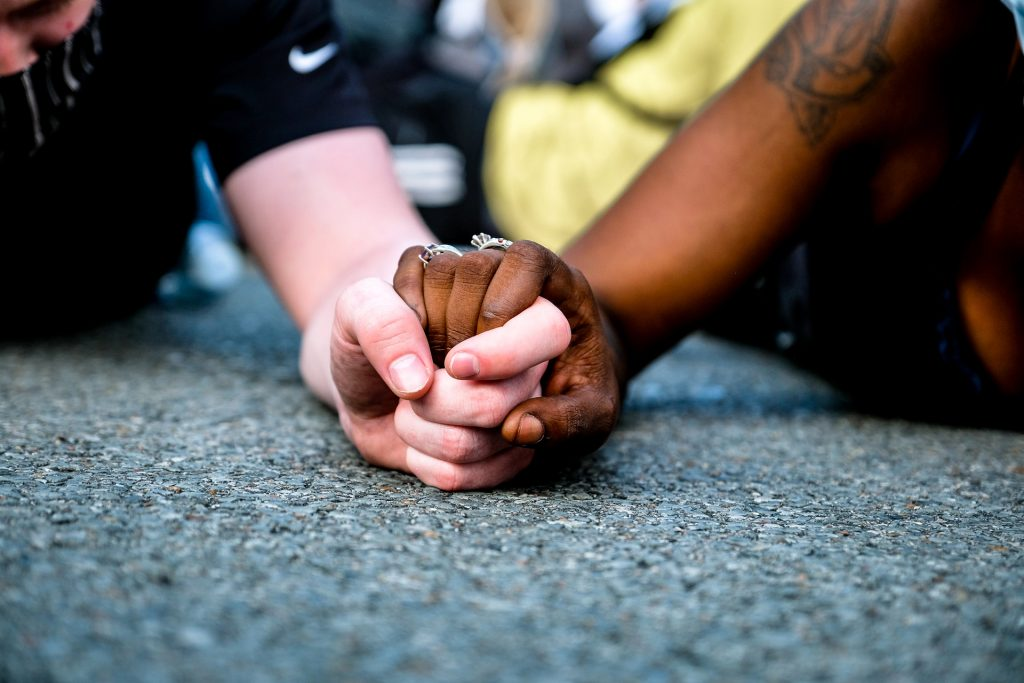 a black youth and white youth clasping hands