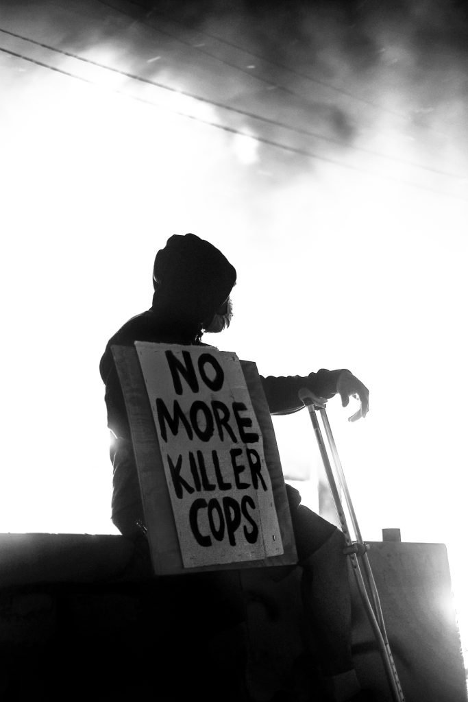 Man holding No More Killer Cops Sign in front of overexposed scene