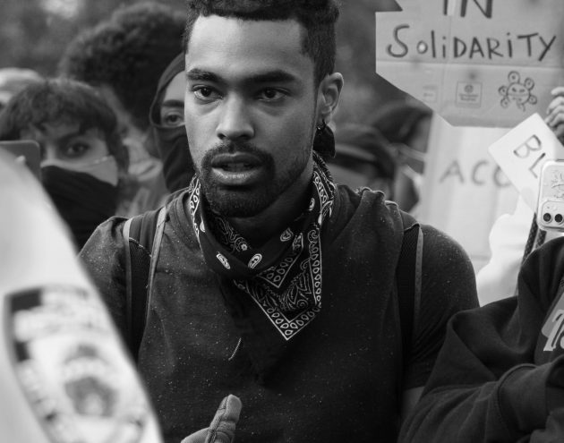 "Young man standing in front of ""Latinx in Solidarity"" sign"